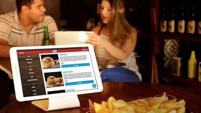 clientes no restaurante com tablet sendo usado para ver o cardápio online