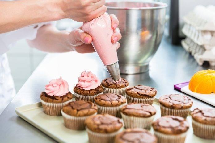 Confeiteira confeitando cupcakes