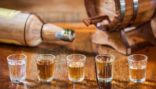 copos de cachaça e barris de madeira